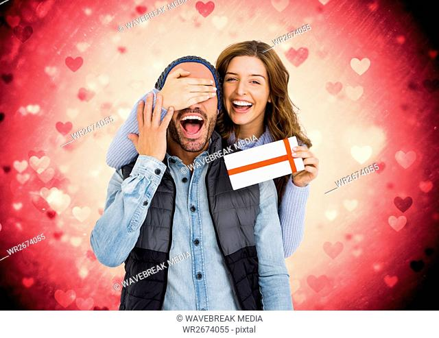 Composite image of happy couple holding a gift card