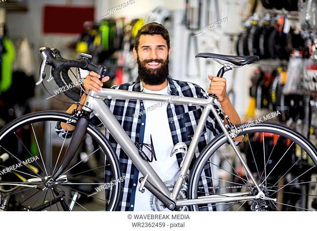 Casual hipster lifting a bicycle