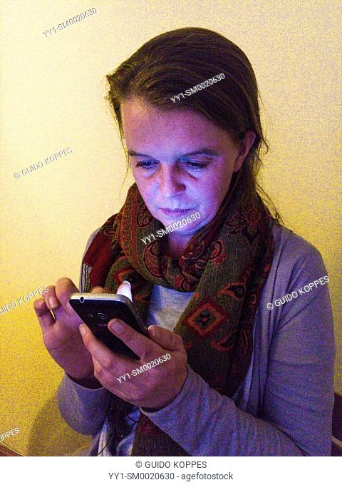 Tilburg, Netherlands. Mid adult woman using her smartphone wile sitting at a dining room table at night