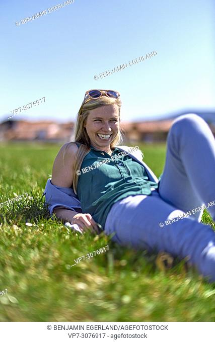 Waakirchen, Bavaria, Germany, woman laying in meadow at country side