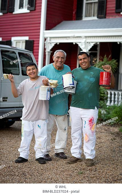 Smiling Hispanic men and boy posing with paint cans and paintbrushes