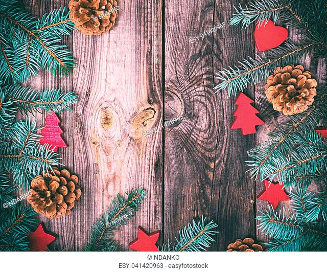 gray wood background with green spruce branches and Christmas decor, empty space in the middle