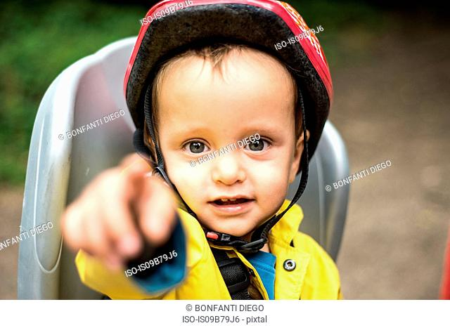 Portrait of young boy sitting in child's seat of adult bicycle, pointing