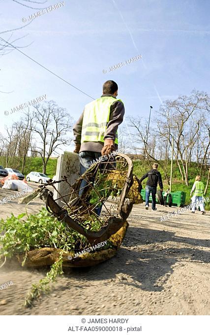 Volunteer carrying rusty mattress to dumpster
