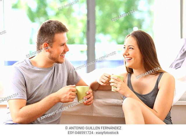 Happy couple talking and having breakfast in an hotel room or home with a green background outdoors