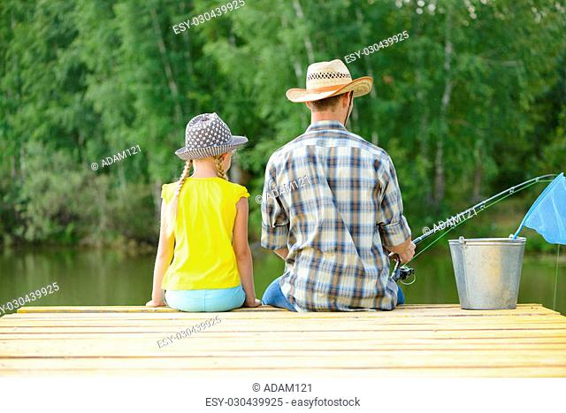 Back view of father and daughter sitting on pier and fishing
