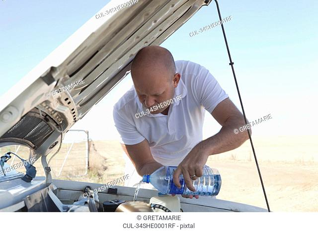 Man pouring water on car engine
