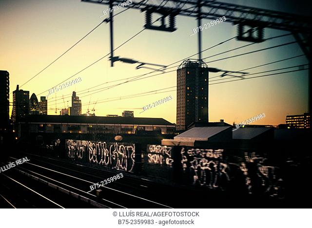 Urban sight at the sunset, from the window of a train with graffiti in the foreground and emblematic buildings at the background