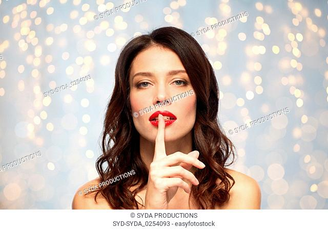 woman with red lipstick holding finger on mouth