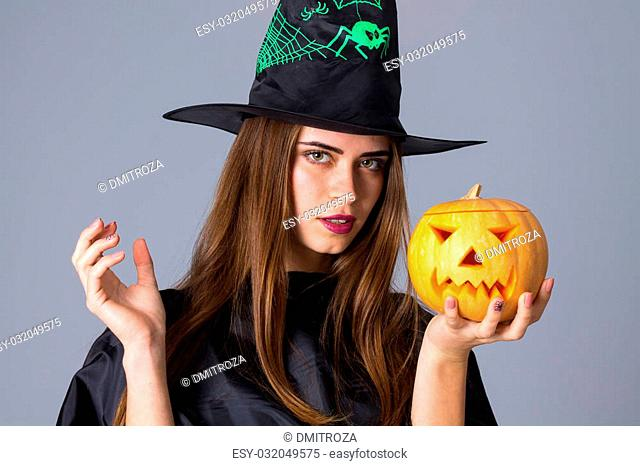 Pretty young woman in black costume of witch with black hat holding a pumpkin on blue background in studio