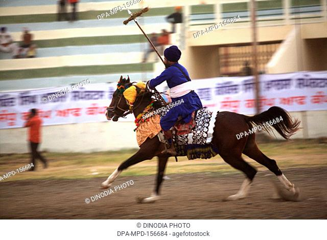 Nihangs or Sikh warriors on his horse showing stunts during cultural events for 300th year's celebrations of Consecration of perpetual Sikh Guru Granth Sahib at...