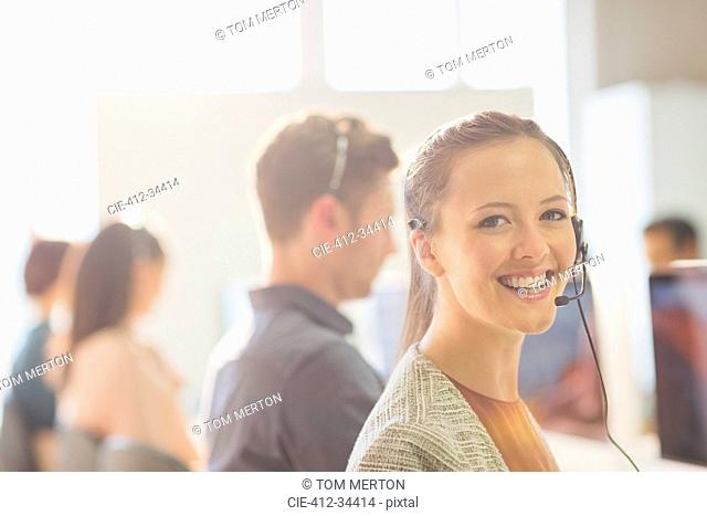 Portrait smiling female telemarketer wearing headset in office