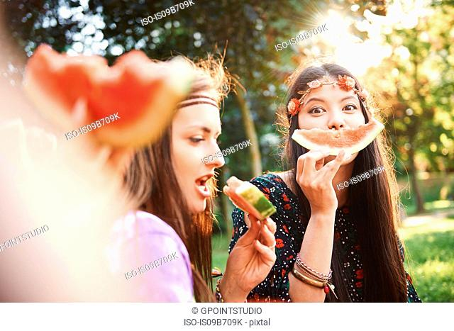 Young boho women making smiley face with melon slice at festival