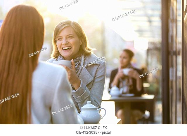 Women laughing and drinking tea at sidewalk cafe