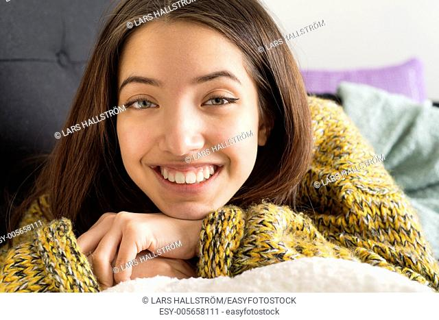 Beautiful teenage girl wearing warm knitted sweater lying on couch