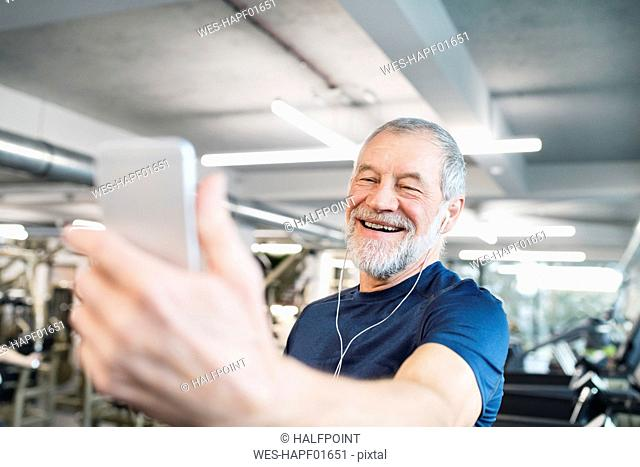 Happy senior man with smartphone and earphones in gym
