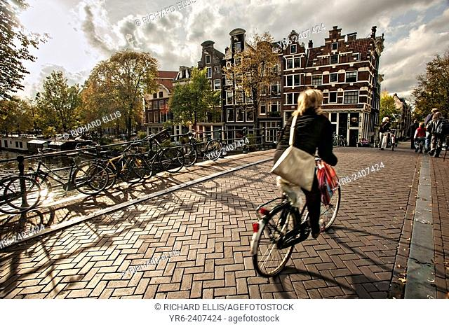Bicyclist crossing the the Hemonybrug bridge at Keizersgracht and Leidsegracht in Amsterdam