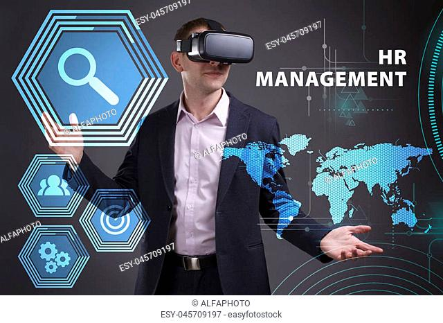 Business, Technology, Internet and network concept. Young businessman working on a virtual screen of the future and sees the inscription: HR management