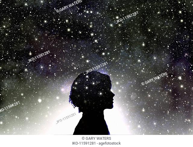 Silhouette of woman's head in galaxy of stars
