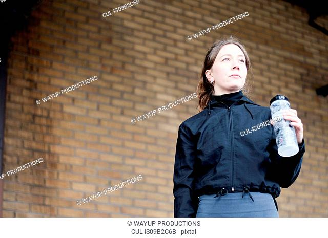 Portrait of young female runner with bottled water