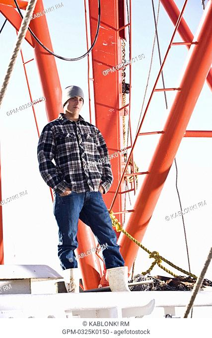 Young fisherman in plaid shirt standing on fishing boat
