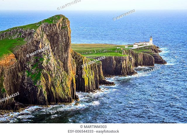 View of Neist Point lighthouse and rocky ocean coastline, highlands of Scotland