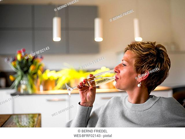 Woman drinking glass of champagne in kitchen at home