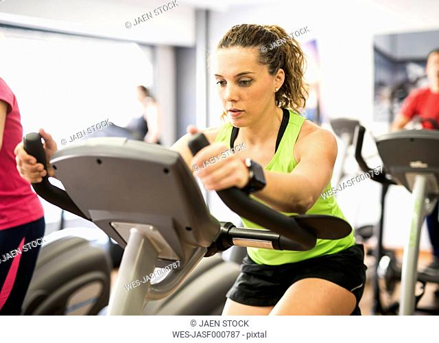 Woman training on exercise bike in gym