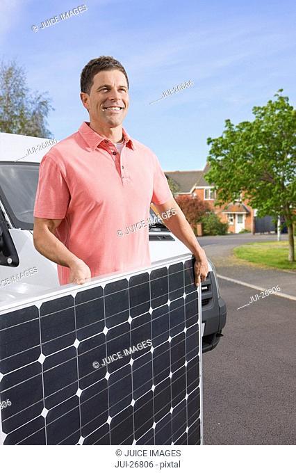 Man carrying solar panel across street