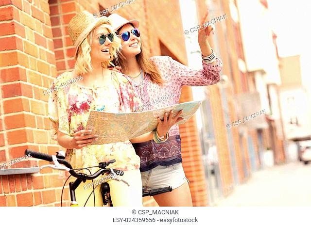 Two girl friends using map while riding tandem bicycle