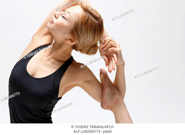 Attractive young Japanese woman wearing black pants and tank top practicing yoga on white background