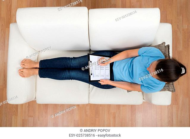 High Angle View Of Woman Sitting On Sofa While Filling Survey Form