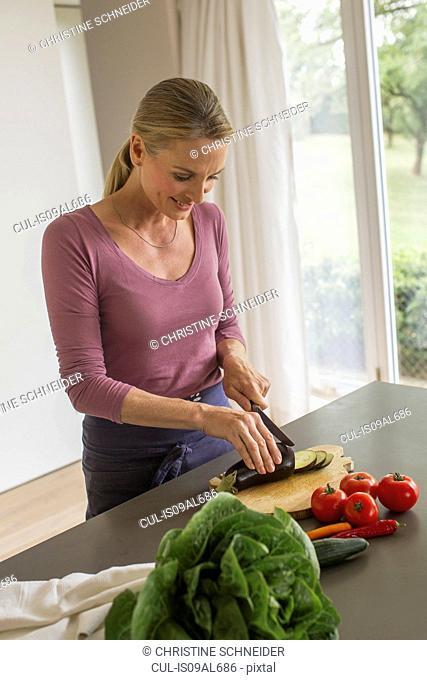 Mature woman slicing aubergine
