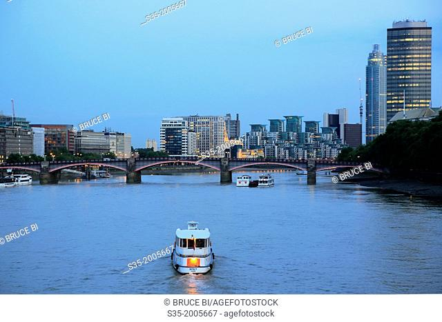 Boat in River Thames with Lambeth Bridge and office towers and apartment buildings in the background, London, England, UK
