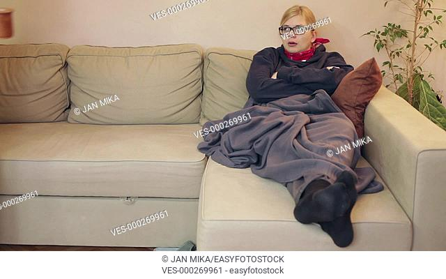 Two ill women resting together on the sofa at home