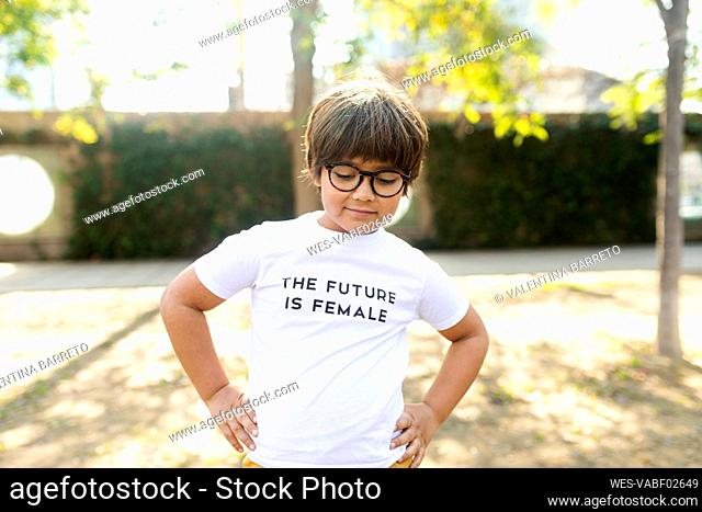 Proud little boy standing in the street with print on t-shirt, saying the future is female
