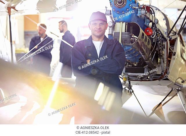 Portrait confident male mechanic working on airplane in hangar