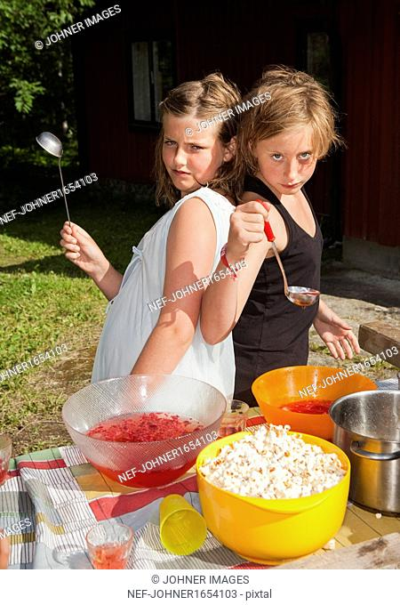 Two girls serving fruit punch outdoors