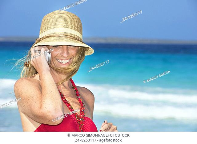 Woman on beach using mobile phone, Formentera, Balearic Islands, Spain