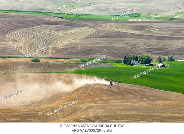 Beautiful scenery of Palouse region with tractor working in field, Washington State, USA