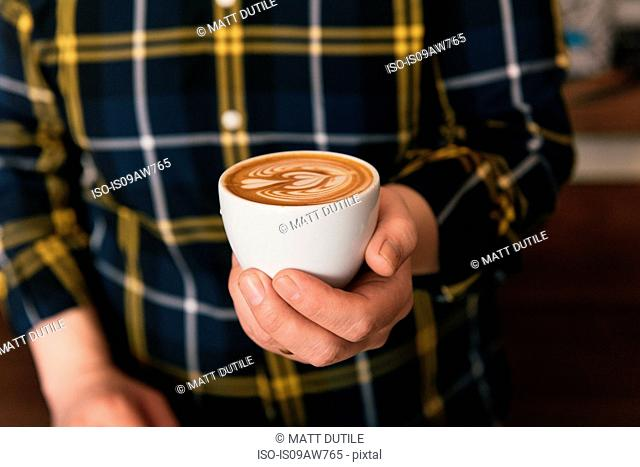 Cropped shot of man wearing checked shirt holding cup of latte