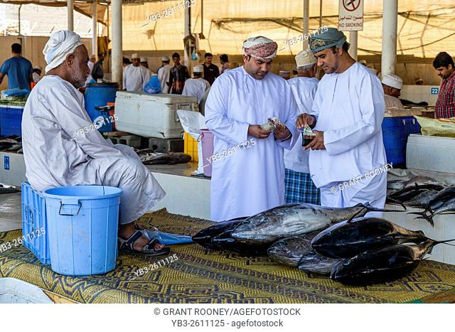 Omani Men In Traditional Costume Buy Fresh Fish At The Fish Market, Muttrah, Muscat, Sultanate Of Oman