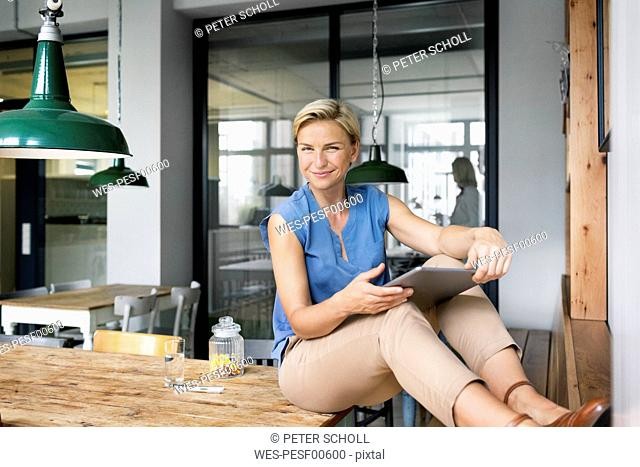 Portrait of smiling blond woman with tablet sitting on table