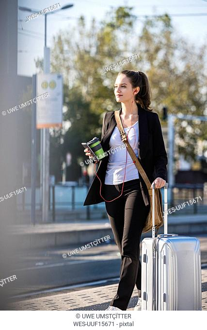 Young woman with luggage at tram station on the move