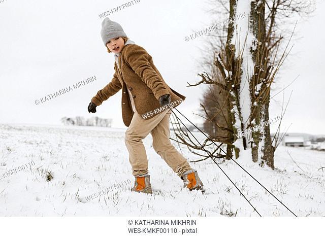 Boy pulling sledge