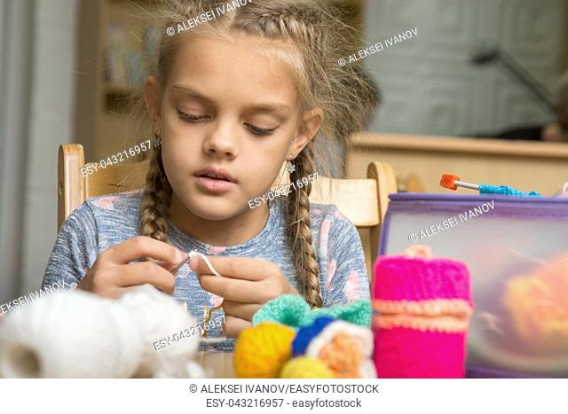 Portrait of a girl enthusiastically engaged in knitting