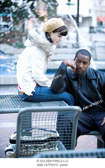 Close-up of a contemplative young inter-racial couple on a park bench