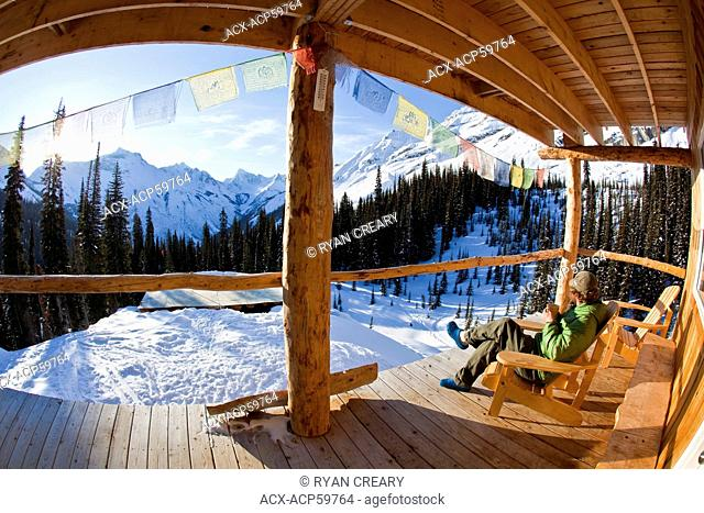 A man enjoying early morning sunrise and a coffee at a backcountry ski lodge. Icefall Lodge, Golden, BC