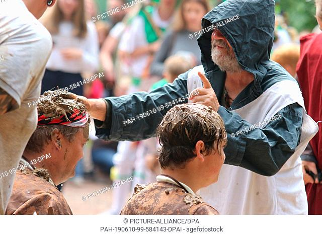 10 June 2019, Saxony-Anhalt, Hergisdorf: At the traditional dirty pig festival, men sit in a mud dump, while a man standing in front of them smears mud on their...