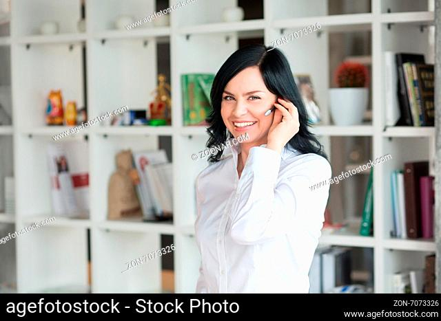 She like to speak with clients on phone. Portrait of white collar worker with headphones in office